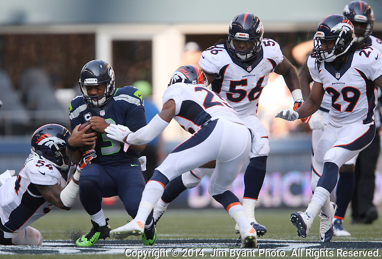 Seattle Seahawks quarterback Russell Wilson (3) scrambles away from the Denver Broncos  linebacker Nate Irving (56), Brandon Marshall (54)) and cornerbacks Chris Harris Jr. (25) and Bradley Roby (29) at CenturyLink Field in Seattle, Washington on September 21, 2014.  Wilson completed 24 of 34 passes for 258 yards, two touchdowns and one interception in the 26-20 overtime win against the Broncos.  ©2014. Jim Bryant Photo. All rights Reserved.