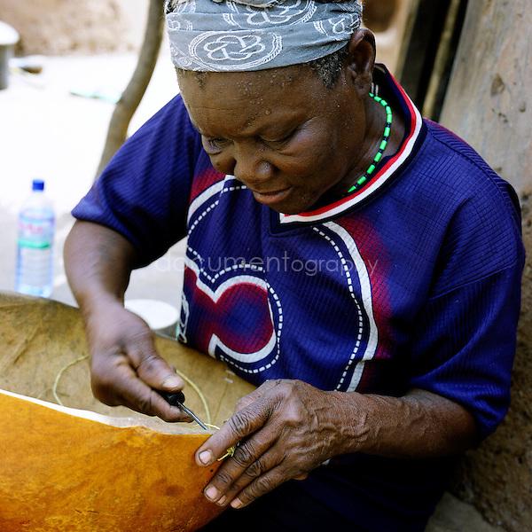 A woman seaming a broken bowl.