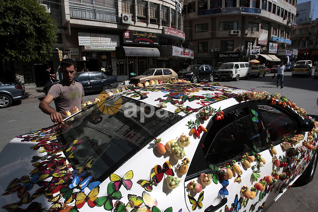 A Palestinian man display magnetic decorations on his car to sell it, at the main market of the West Bank city of Nablus, on May 22, 2013. Photo by Nedal Eshtayah