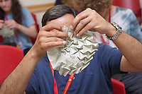 New York, NY, USA - June 24-25, 2017: OrigamiUSA 2017 Convention at St. John's University, Queens, New York, USA. Alessandro Beber, Italy, teaches a class how to fold his complex 1-Cube Tessellation. The Challenge: Sachin Shah, Illinois, works on his model.