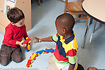 Education preschool 3 year olds two boys playing with duplo train one boy offering another a piece handing it to him horizontal