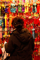 Woman shopping for Chinese decorations at Chinese New Year 2011 celebrations in Tinseltown Mall, Chinatown, Vancouver, BC, Canada..