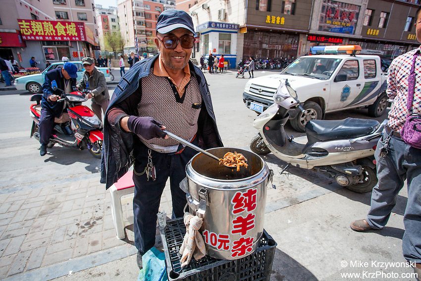 Street vendor holding a spoonful of meat that he is selling meat in Datong, China