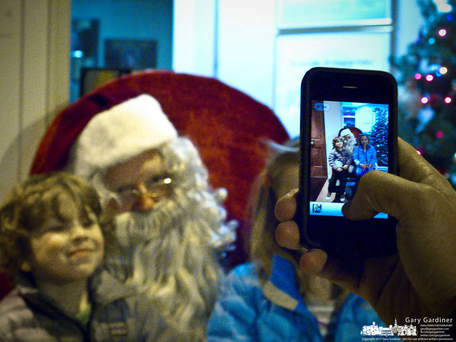A mother uses her cell phone camera to take a photo of her children sitting on Santa's knee after his arrival at the Christmas Tree lighting ceremony.