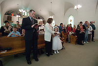 Families stand during first communion sacrament services at a Catholic church in Johnstown, OH.<br />