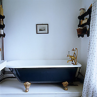 A blue ball-and-claw bath with brass taps
