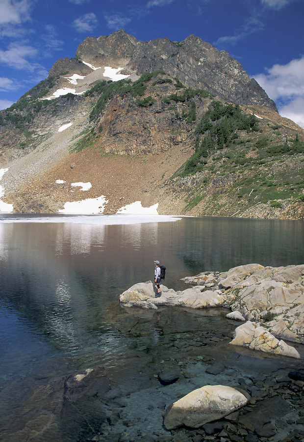 Woman at lake below mountain, Washington