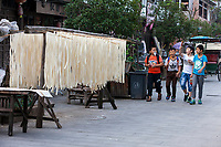 Yantou, Yongjia, Zhejiang, China.  Teenage Boys Walking Home after School.  Noodles Drying on Poles on Left.