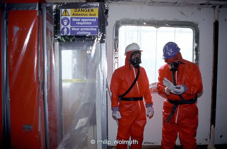 Workers using breathing apparatus and protective clothing prepare to remove sprayed asbestos from a Chantry Point, a condemned high rise residential building on the Elgin Estate in West London. The building was used by Westminster City Council, under the leadership of Dame Shirley Porter, to house homeless families. It was demolished by Walterton and Elgin Community Homes (WECH), after the resident-controlled housing association took over the estate.