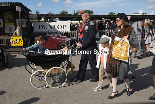 """Goodwood Festival of Speed. Goodwood Sussex. UK. Retro dressing man. Neil Reynolds 48yrs old  pushing a 1957 Marmet pram with daughter 5 yr oldf Pipper. He is wearing his fathers 23rd Hussars officers uniform. His 6th revival. """"They get better everytime."""""""
