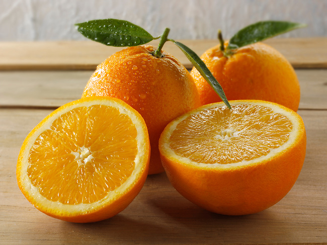 Whole and cut fresh oranges