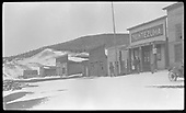 Snow-covered street of small single-story false front buildings, stores, saloons and offices.  Front end of early auto is seen on right.<br /> Elizabethtown, NM  Taken by Newman, Almeron
