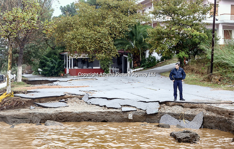 A police officer by a road that has collapsed in Nea Mihaniona