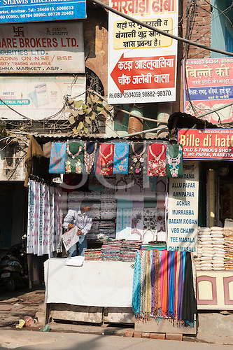 Amritsar, Punjab, India. Street scene; colourful roadside stall selling t-shirts, tablecloths and other textiles with a jumble of trade signs above in western and Hindi script.