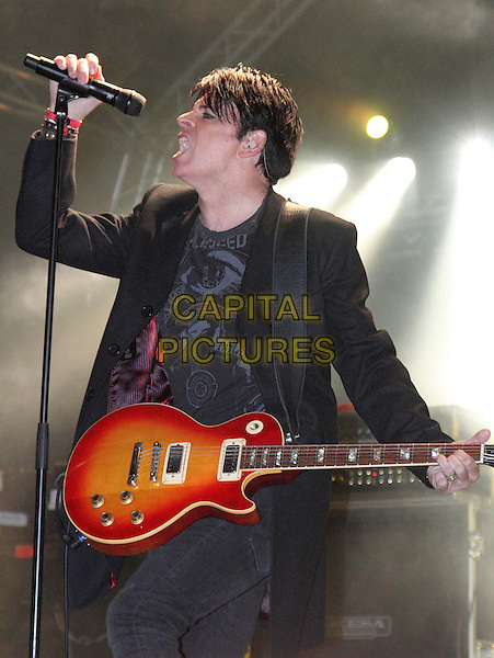 Gary Numan.Guilfest 2012- Day 2, Stoke Park, Guildford, Surrey, England..July 14th 2012.on stage in concert live gig performance performing music half length black top suit guitar hand arm side profile singing microphone .CAP/JIL.©Jill Mayhew/Capital Pictures..