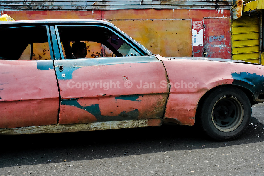 A rusty and damaged American classic car from 1970s, used as a shared taxi, seen parked in Maracaibo, Venezuela, 10 May 2006.