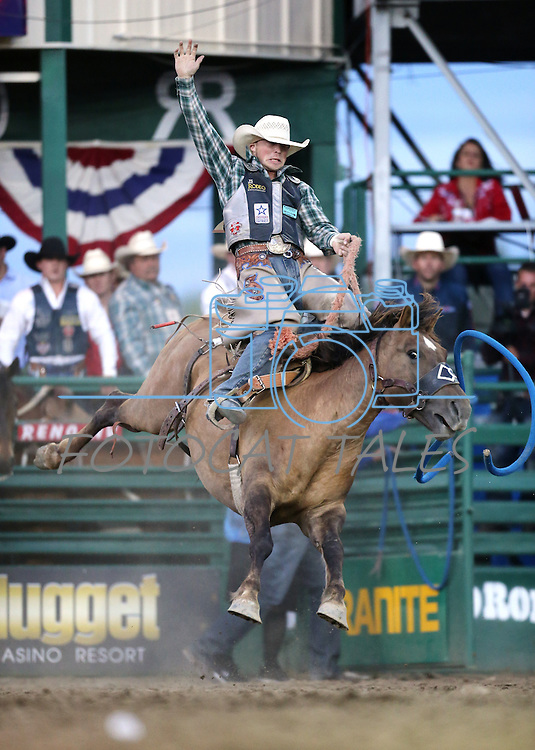 Tyrell Smith rides in the saddle bronc competition at the Reno Rodeo in Reno, Nev. on Friday, June 19, 2015.<br /> Photo by Cathleen Allison/Nevada Photo Source