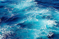 Abstract image of brilliant blue Caribbean waters disturbed by the passage of cruise ship.