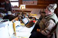 Communication volunteer Pete Semenya on watch inside the community center at the village checkpoint of Ruby during the 2010 Iditarod