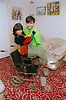 Man lifting female wheelchair user into chair,