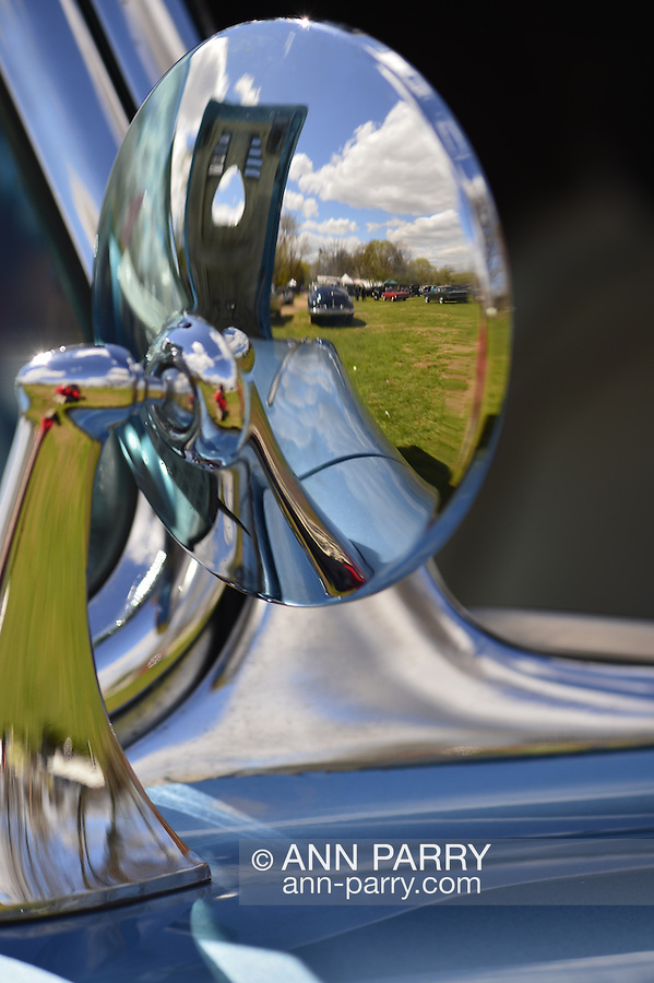 Floral Park, New York, U.S. - April 27, 2014 - The 1961 Chevrolet Corvette convertible rear view mirror reflects a beautiful blue sky over the field at the 35th Annual Antique Auto Show at Queens Farm.