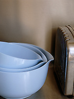 A set of three mixing bowls in descending size beside a stainless steel toaster
