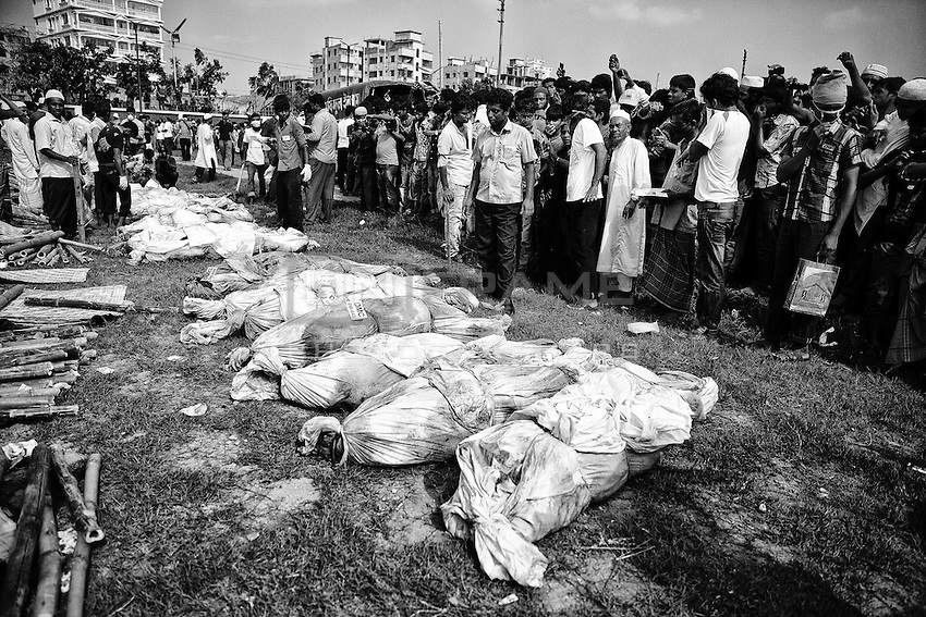 Bodies of unidentified garment workers, who died in the collapse of the Rana Plaza building in Savar, lie on the ground as people gather to watch a mass burial in Jurain graveyard, Dhaka, Bangladesh.