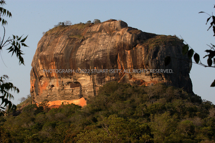 5/16/2003--Sigiriya, Sri Lanka..The Sigiriya  Rock city dates back from over 7,000 years ago, through Pre-Historic to Proto-Historic to Early Historic times, then as a rock-shelter mountain monastery from about the 3rd century BC, with caves prepared and donated by devotees to the sangha...The garden city and the palace was built by Kasyapa 477 - 495 AD. Then after Kasyapa's death it was a monastery complex upto about the 14th century. ..The Mahavamsa, the ancient historical record of Sri Lanka, describes King Kasyapa as a parricide, who murdered his father King Dhatusena by walling him up alive and then usurping the throne which rightfully belonged to his brother Mogallana. To escape from the armies of Mogallana, Kasyapa is said to have built his palace on the summit of Sigiriya, but Mogallana finally managed to get to Kasyapa and he committed suicide...All photographs ©2003 Stuart Isett.All rights reserved.This image may not be reproduced without expressed written permission from Stuart Isett.