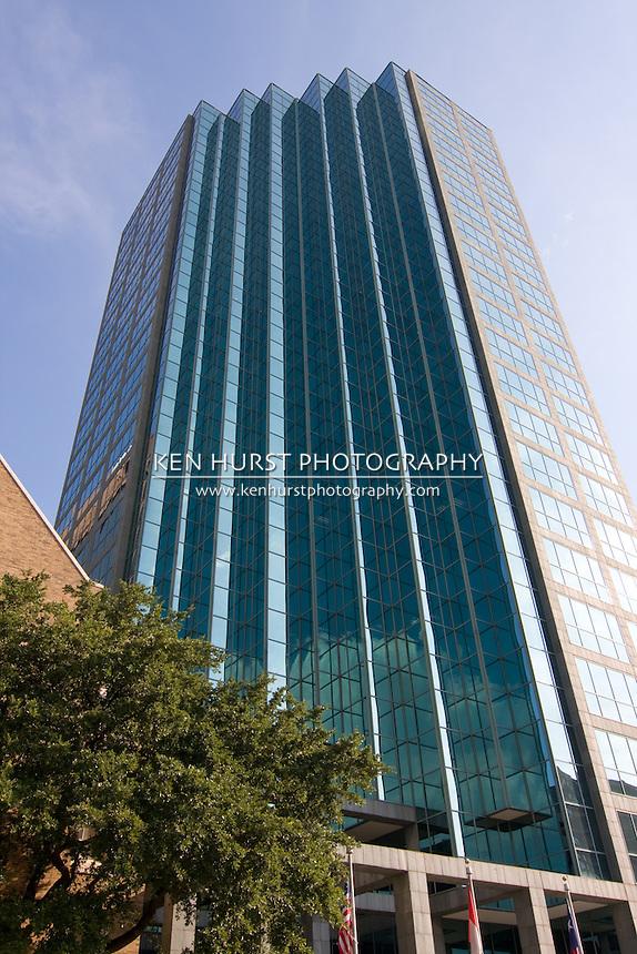 City skyscraper rising majestically into a beautiful blue sky.