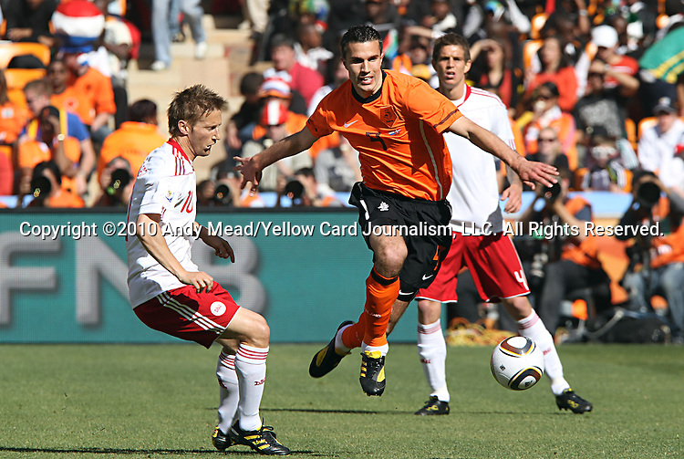 14 JUN 2010:  Robin van Persie (NED)(9) jumps over the feet of Martin Jorgensen (DEN)(10) as he moves the ball forward.  The Netherlands National Team led the Denmark National Team 1-0 at the end of the 1st half at Soccer City Stadium in Johannesburg, South Africa in a 2010 FIFA World Cup Group E match.