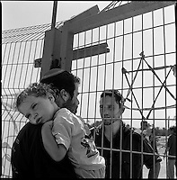 Shirat Ayam Settlement, Gaza strip Israel, Aug. 2005 .A settler discusses the forthcoming evacuation with his brother, a captain in the army, across the settlement gate.