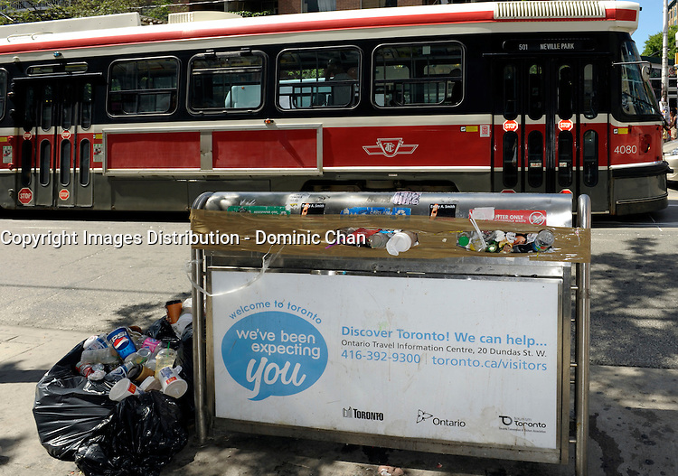 Toronto (on) CANADA, July 4, 2009  Toronto Garbage Strike - full garbage can on Queen Street West with TTC street car in the background.