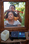A woman looks in a mirror as her hair gets styled outdoors in Mizak, a small village in the south of Haiti.