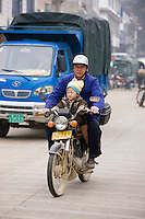 Man and child on a motorbike on market day in the town of Baisha, near Guilin, China