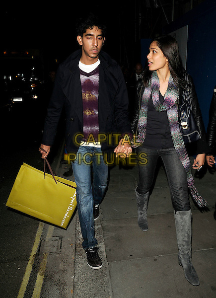 DEV PATEL & FREIDA PINTO.Spotted out and about near Conduit Street, London, England, UK,.October 20th 2009..full length couple holding hands Rupert Sanderson shopping bag jeans grey gray boots purple green knitted scarf black coat bag knee high jumper .CAP/CAN.©Can Nguyen/Capital Pictures.