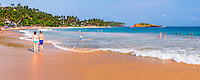 Panoramic photo of tourists walking along Mirissa Beach, South Coast of Sri Lanka, Asia. This is a panoramic photo of a tourists walking along Mirissa Beach, Sri Lanka, Asia. Mirissa Beach is popular with tourists due to its beautiful sand and palm trees.