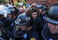 Unite the Right rally organizer Jason Kessler is escorted by police after his press conference was disrupted by protestors Sun., August 13, 2017 outside City Hall in Charlottesville, Va. The previous day, a woman was killed and several others injured after the Unite the Right rally. Photo/Andrew Shurtleff
