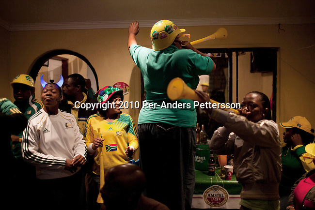 SOWETO, SOUTH AFRICA - JUNE 11: South African soccer fans celebrate a goal by the South African national team on June 11, 2010 in bar in the Orlando West section of Soweto, in South Africa. South Africa played Mexico in the opening game and the final score was 1-1. South Africa didn't advance past the group stage in the 2010 World Cup, held in their own country. In hosting the largest sporting event in the world, South Africa has a chance to impress the world with their country, hoping that the month long event will bring long lasting benefits for the country. (Photo by Per-Anders Pettersson)