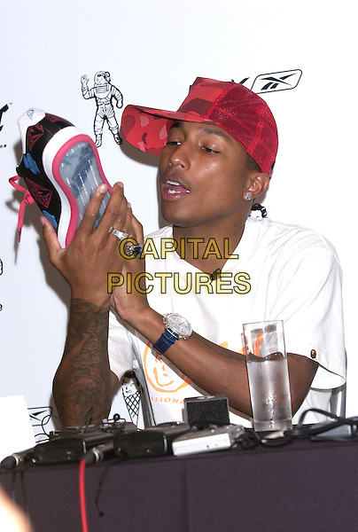 "PHARRELL WILLIAMS.of the neptunes and N.E.R.D lauches new clothing range ""Billionaire Boys Club"" and ""Ice Cream"" footear collection in association with RBK, a division of the Reebok group, London,.August 23rd 2004..half length red trucker cap tattoo ring watch holding shoe trainer.Ref: PL.www.capitalpictures.com.sales@capitalpictures.com.©Capital Pictures."
