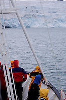 Ecotourist standing on ships bow looking at glacier in isfjorden on Spitzbergen, Arctic Norway