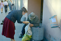 Saint Petersburg, Russia, August 2002..A woman pauses on Nevsky Prospect to give a homeless man a loaf of bread. Fyodor Dostoyevsky,  chronicler of Russia's under class, would still recognise much in his native city. The streets he knew still teem with thieves, drunks, homeless & those on the fringes of society..
