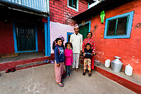 A family outside their small house in the lower mountains of the Himalayas, near Pokhara, Nepal.
