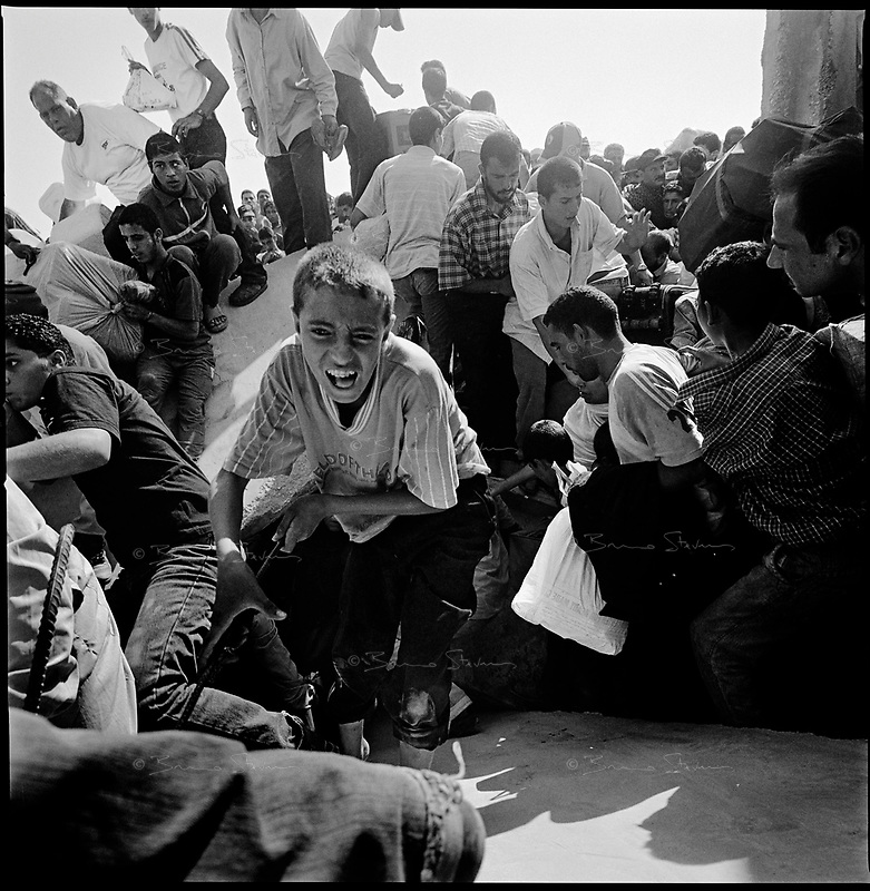 Rafah, Gaza strip, Sept 14 2005.The Hamas blew up a section of the 8 meter high wall separating the Palestinian city from Egypt. Thousands  rushed across the border in an incredible chaos to visit relatives for the first time in 18 years or ... to bring back cheap Egyptian goods such as cigarets or gazoline.