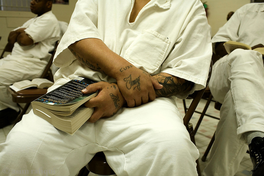 A bible study session with Pastor Daniel - men with gang tattoos and a bible Inmates at the carol s. vance prison in sugarland, texas during a bible study session.  the carol s. vance unit is one of the handful of prisons in the USA managed by evangelical christian pastors who use a bible-centered program for rehabilitation and counseling.  from daybreak to lights out, the prisoners are put through a series of spiritual and religious exercises, lectures, discussion groups asked to bring christ back into their life.  the program is also the prisoner's principal if not the only support chain once they leave the prison and return to society.