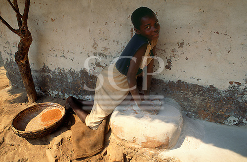 Kapatu, Zambia. Girl making millet flour in the traditional way with a stone on a hard baked adobe base.