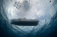 View from underwater looking up at a moored dive boat on Roatan, Honduras.
