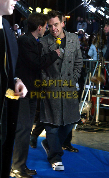 "ROBBIE WILLIAMS.Attends ""ECHO"" in Berlin.Ref: Wiese .microphone, interview, reporter, grey coat, gray coat, full length, full-length.www.capitalpictures.com.sales@capitalpictures.com.©Capital Pictures"