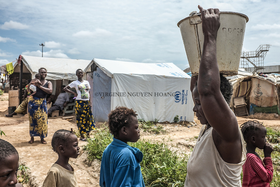CAR, Bangui: A woman just took some water from the well where people from te Mpoko camp can take water for their garden and their laundry. 17th April 2016.<br /> RCA, Bangui : Une femme a pris un peu d'eau du puits o&ugrave; les gens du camp Mpoko prennent de l'eau pour leur jardin et leur linge . 17 avril 2016.