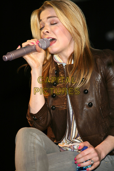LeANNE RIMES.Country Radio Seminar (CRS)  Songwriters known as KCRS, Nashville, Tennessee, USA, 05 March 2008..half length brown leather jacket singing microphone on stage sitting performing concert gig .CAP/ADM/RR.©Randi Radcliff/Admedia/Capital Pictures
