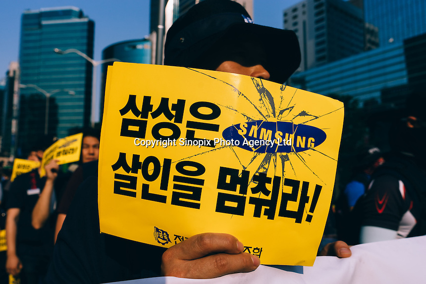 "SEOUL, Korea, May 30 - A worker holding up a sign ""Samsung, stop killing!"" marches in protest through pavements of Gangnam in front of SamsungHQ.<br /> <br /> The sign refers to a recent suicide of a union worker, as well as leukemia and other illness victims from Samsung semi-conductor plants."